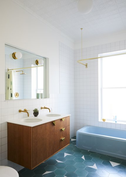 The renovation introduced green cement floor tile from Clé, a custom vanity with triangular brass pulls, and square wall tile that echoes the ceiling pattern.