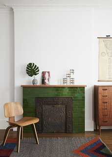 The designers refurbished this fireplace surround with deep green Waterworks tile, so as to remain consistent with the color palette used throughout the house.