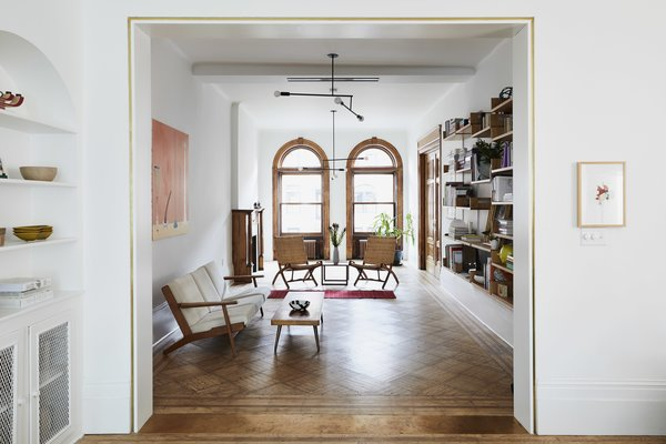 """The architects widened the opening between the living room and dining room, then delineated it with brass accents. """"Rather than try to match the existing historical moldings, we opted for minimal trim with brass inlays and a broad brass threshold marking the new opening,"""" they said. The pendent lights are by Andrew Neyer."""
