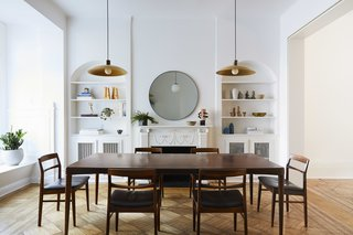 """The dining room is a transitional space between the old and new—in this space we simplified the material palate, painting all decorative woodwork matte white to emphasize its geometry over its materiality,"" say the architects. The room holds a midcentury dining set and pendent lights from Raco."