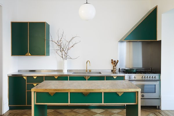 Modern green cabinetry contrasts brightly with the home's historic shell. Custom triangular brass pulls designed by the architects echoe the brass accents on the nearby threshold between the living and dining rooms. The island top is Marmoleum, while the counter along the wall is stainless steel, which syncs with the Bertazzoni range.
