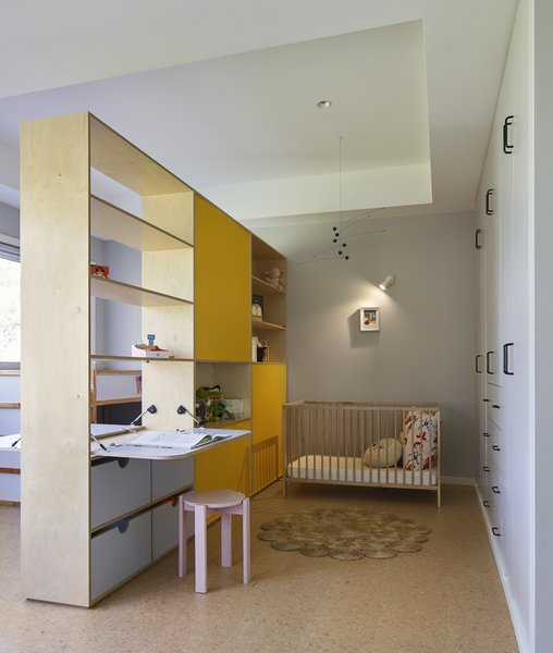 """One of the existing bedrooms was so big, it could easily become the bedroom for both children,"" said the firm. ""A custom shelving unit became a screen, as well as a series of shelves, nooks, and desk spaces."""