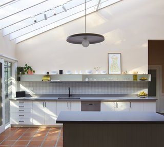 In the kitchen of Selby Aura, Drawing Room Architecture painted the existing cabinetry and kept the hardware. They installed new Caesarstone raw concrete composite stone counters, a tile backsplash, and a custom wall shelf.