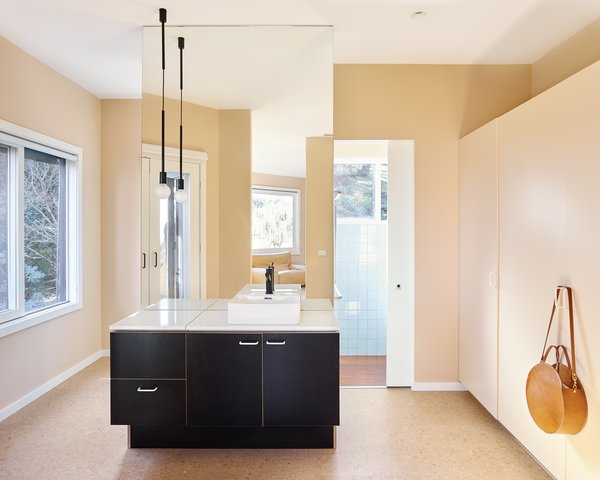 The designers rebuilt the vanity with MAXI Film birch plywood in black, and a Caesarstone raw concrete composite stone counter.