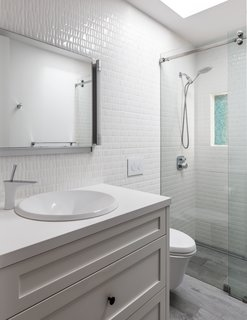 The distinctive tile pattern in a bathroom echoes the pattern treatment on the base of the kitchen island.