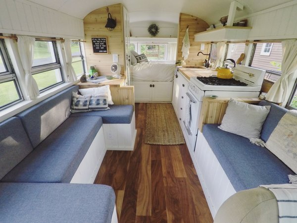 "The bus has a seating area, kitchen, and bed propped over the ""garage,"" where the couple stores their gear. Mande did all the sewing herself, using foam from the old seats to make the built-in couches. ""This is a space for slowing down, simplifying, and clearing the mind,"" say the couple."