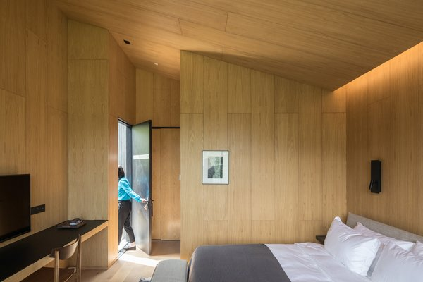 Wood paneling wraps the interior of a trapezoidal cabin.