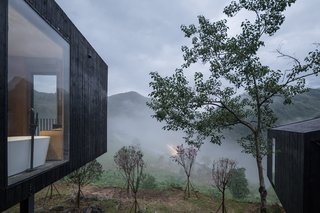Each cabin is constructed from an elevated steel platform with charred wood siding. A footpath connects them.