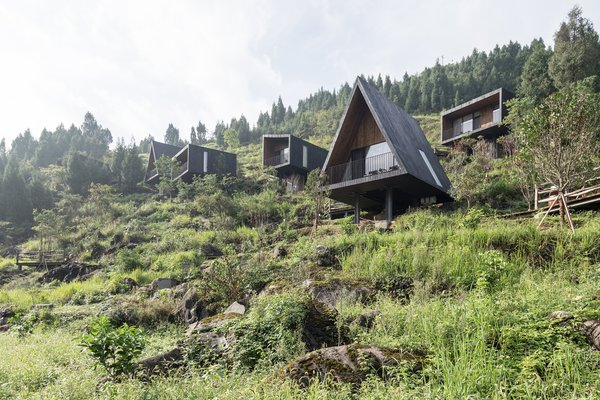 """The cabins share a common interior and exterior material palette for consistency, and to better allow them blend in with the hillside. """"The design of the wood houses aims to harmonize with the landscape and the rustic atmosphere while forming a contrast to the existing village buildings,"""" says the firm."""