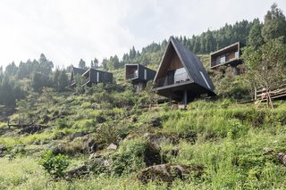 "The cabins share a common interior and exterior material palette for consistency, and to better allow them blend in with the hillside. ""The design of the wood houses aims to harmonize with the landscape and the rustic atmosphere while forming a contrast to the existing village buildings,"" says the firm."