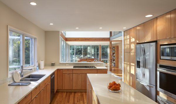 The renovated kitchen features quartz counters and natural maple cabinets, and it flows easily with the rest of the renovated open plan.