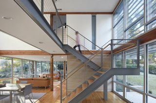 A new steel staircase with wood tread and a cable railing does not block views outside. The double-height window systems used at the front and back of the home are glass storefront units from YKK.