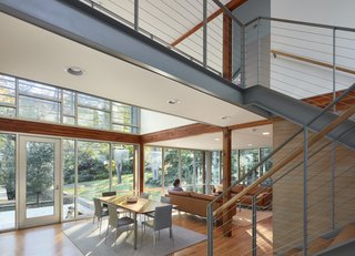 The view from the entry now encompasses open and airy living spaces that connect to the garden via floor-to-ceiling glass.