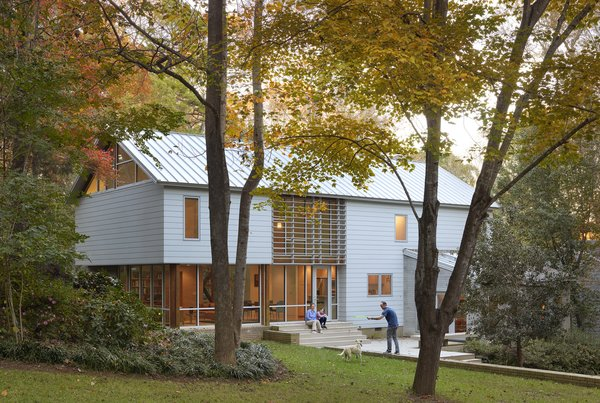 """Kranbuehl landscaped the previously forested backyard with a """"grass terrace"""" and masonry walls, so that the exterior felt of a piece with the interiors. Trees and hedges still stand on the perimeter to create natural screening from the neighbors."""