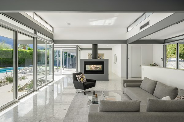 The home's key features are its post-and-beam construction, deep overhangs to modulate light and shadows, open-plan interiors, and easy indoor/outdoor flow via floor-to-ceiling sliding doors.