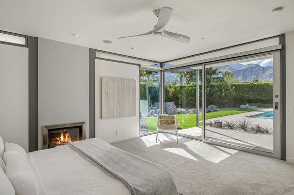 The home has three bedrooms. This one has framed views of the backyard, as well as a bedside fireplace.