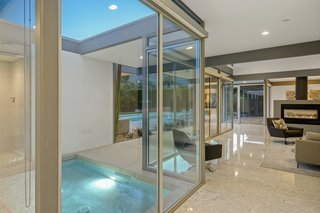 An in-ground water feature is surrounded by atrium-like glass walls that keep the interior feeling open and airy.
