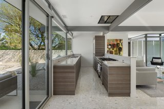 A hard-working galley kitchen with wood cabinets and stone counters.