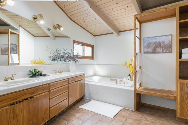 The master bathroom has a simple tile treatment and wood storage units.