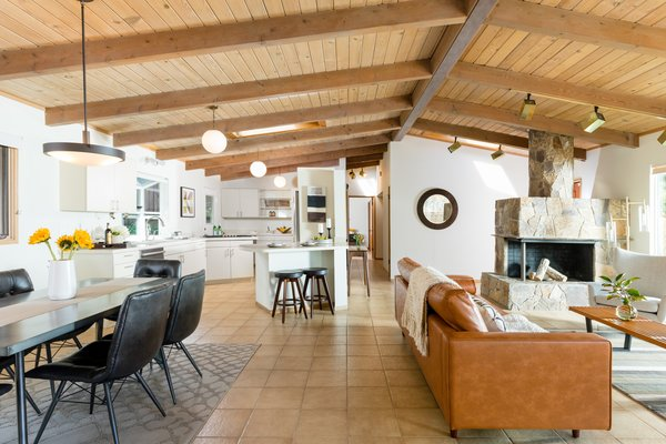 The simple white kitchen anchors the corner, with an eat-in bar for informal meals. Skylights bring lots of natural light into the room, as well as circulation areas like the hall and entryway.
