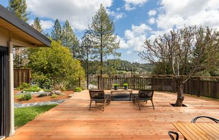 A redwood deck, easily accessed from the living areas, is a nice spot for alfresco meals or outdoor hangs, with views overlooking the hills and city lights.