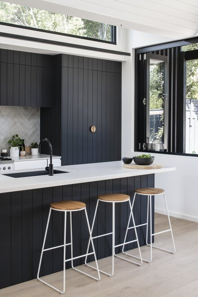 "The dark kitchen cabinetry is a nod to the exterior, ""as the pattern of the shiplapped cladding informed the grooves of the kitchen joinery,"" says the firm."