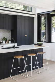 The dark kitchen cabinetry is set off by a marble tile backsplash in a herringbone pattern in this Australian kitchen.