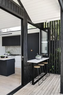 A pass-through serving window positioned between the kitchen and deck facilitates indoor/outdoor flow and makes grilling and entertaining easy.