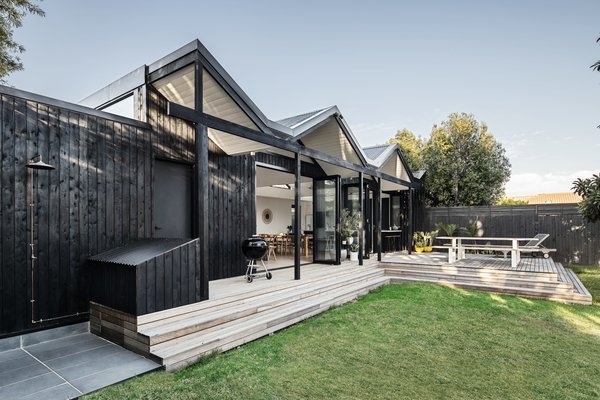 """The brief was to efficiently and cost effectively transform a light-starved weatherboard into an open and modern home with a good connection to the rear garden and a relaxed yet refined feel,"" says the firm. The owner charred and oiled the shiplapped cypress siding himself."