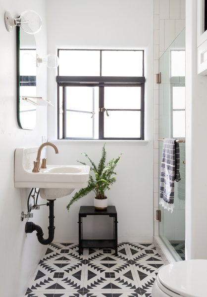 Black-and-white cement tile syncs with the kitchen tile, and maintains the high-contrast motif throughout. A gold faucet gussies up the old sink, and a new mirror and sconces bring in more style than the clinical versions before.