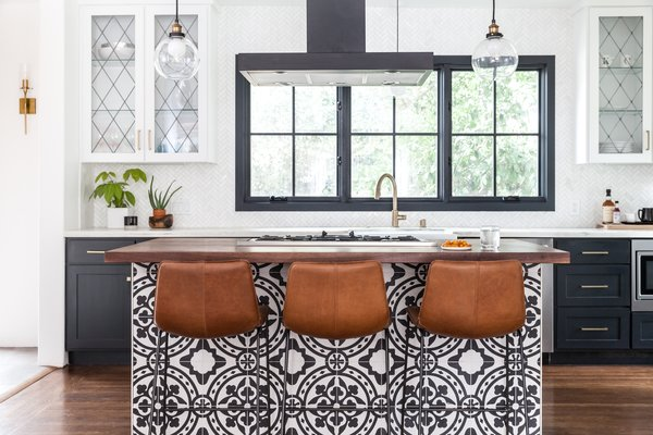 The new kitchen has much more elbow room and an eat-in bar clad in graphic, black-and-white tile. Carrera marble tile laid in a herringbone pattern covers the backsplash, while the counters are honed marble, at the back, and walnut, at the island.