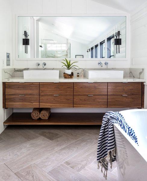 An engineered quartz counter tops a custom walnut vanity.