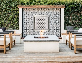 A close-up of the fire pit lounge area with the water feature outfitted in cement tile, making a lovely backdrop that ties together with the interior finishes.