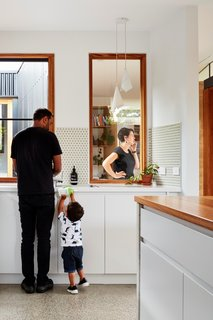 """In the kitchen, flat-front cabinetry from MTR joins Inax' round <span style=""""font-family: Theinhardt, -apple-system, BlinkMacSystemFont, """"Segoe UI"""", Roboto, Oxygen-Sans, Ubuntu, Cantarell, """"Helvetica Neue"""", sans-serif;"""">Pom Ponette</span><span style=""""font-family: Theinhardt, -apple-system, BlinkMacSystemFont, """"Segoe UI"""", Roboto, Oxygen-Sans, Ubuntu, Cantarell, """"Helvetica Neue"""", sans-serif;"""">backsplash tile</span><span style=""""font-family: Theinhardt, -apple-system, BlinkMacSystemFont, """"Segoe UI"""", Roboto, Oxygen-Sans, Ubuntu, Cantarell, """"Helvetica Neue"""", sans-serif;"""">with a slightly transparent pastel glaze.</span>"""