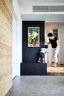 The firm placed an entry hall at the nexus where the addition meets the original house, with the door to the master suite on the left. Built-in storage, here clad in charred wood, is designed for flexibility of use and accessibility to children and adults alike.