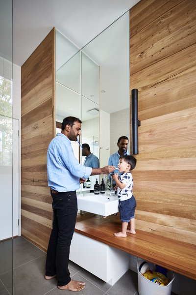 In the bathroom, wood-paneled walls mimic the striations in the rammed earth walls. The wood is wormy chestnut from Urban Salvage in Melbourne, and the counter is recycled blackbutt.