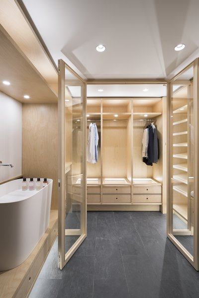 A dressing room continues the high-contrast theme with stone flooring and blonde wood fittings.