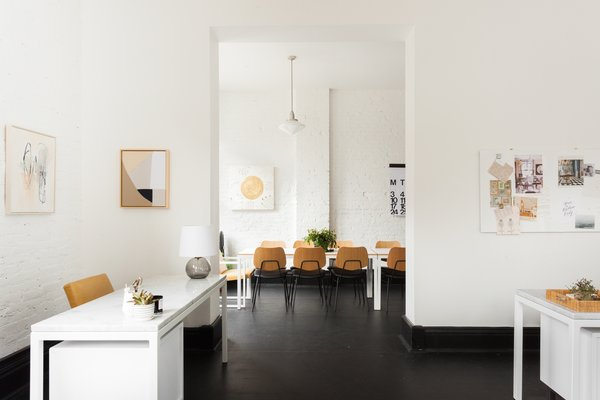 "The office had previously housed an architecture firm that had implemented a high-contrast palette of white brick walls and black-painted trim and flooring. ""Aesthetically, our two goals with the interior were to bring a little warmth to the black and white space with materials like wood and leather, and to keep the palette neutral in every way,"" says LaValle."