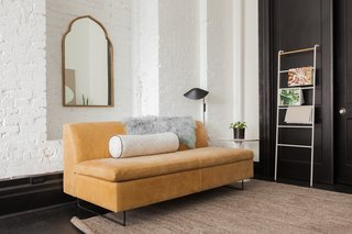 In the lounge area, the Clyde leather sofa from Blu Dot is joined by a Wayfair magazine rack and Saarinen side table.