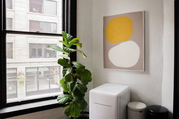 LaValle worked with a good friend and colleague Sarah Hurt of Seattle Art Source to find pieces for the studio, many of them by local artists. In a corner of the kitchen, a piece by the Portland, Oregon–based Mia Farrington hangs above a Daewoo fridge and trashcans by Brabantia.