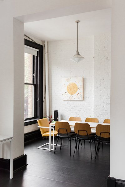 At the conference area, a Pratt Conference Table from Room & Board is surrounded by the Versus chair from Article. The wall artwork is by the Seattle–based Jennifer Ament.