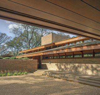 """After: The front door is tucked into the brick facade—a material choice made by Fredrick. Per the architects: """"Walls are constructed of Norman brick manufactured by the Claycraft Company, who also provided bricks for Eero Saarinen's house in Cranbrook, Michigan."""""""