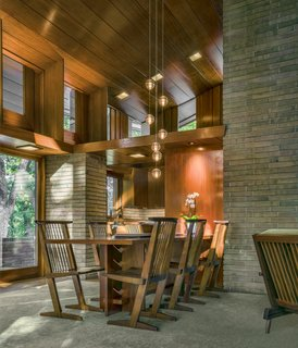 Major interior moves include restoring the tinted concrete flooring throughout, as well as the abundance of Philippine mahogany in the ceiling, walls, and cabinetry. The team also built custom furnishings designed by Wright, such as the dining room table, here surrounded by Nakashima chairs.