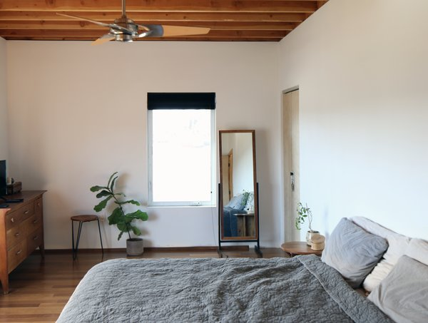 The bedroom maintains the simple palette with windows fabricated by the homeowner and Brazilian walnut flooring.