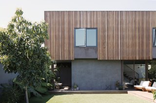 "The 1000-square-foot ADU is two levels with a footprint that allows the owners to retain plenty of outdoor space for their dogs to play. The façade ""is a rain screen system, so the heat gain on the Brazilian hardwood is minimized by being physically separated by an air gap between it and the membrane behind it,"" said Knight. ""So, the wood heats up when sun hits it and this is not directly translated into the wall on the interior; it is instead buffered by this air gap."" The large doors and second-story skylights then work together to pull a nice breeze through the house."