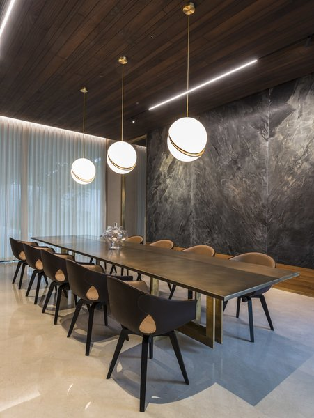 Marble slabs adorn the wall, and bespoke lighting illuminates the table in the dining room.