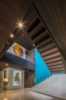 Wood stairs and walls warm up the double-height volume of the stairwell. Custom artwork can be found throughout the home.