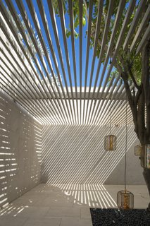A roof of horizontal slats filters the harsh light and creates moody shadows.