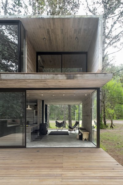 "Luciano Kruk perforates a concrete volume with glass walls to fashion a simple yet elegant vacation home in the province of Buenos Aires. On a quiet lot populated with aged pinewood, Luciano Kruk designed a modest vacation home for three sisters and their families. The 807-square-foot, two-level home is ensconced in its forest setting. The firm employed board-formed concrete inside and out to connect the building with its environment. ""Pine planks were used to set the formwork so that the partitions, as well as the slabs, would preserve the texture of the wood veins in an attempt to establish a harmonious dialogue with the bark of the local trees,"" said the firm."