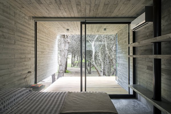 "The master bedroom opens onto a semicovered outdoor patio, shared with the adjacent bunk room. ""In its minimum scale, the house rises by its own will, but also integrates itself respectfully with its surroundings, both natural and human-built,"" said the firm."